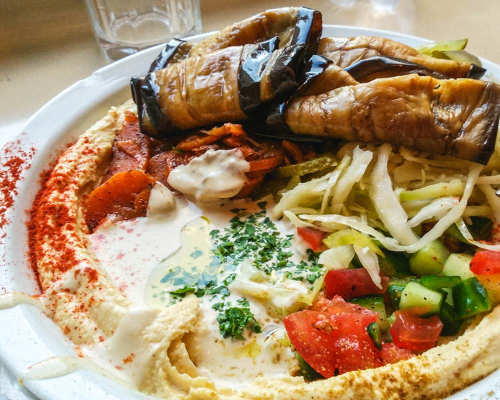 piatto di verdure miste con hummus, melanzane, pomodori, carote e verza budapest vegana e senza glutine