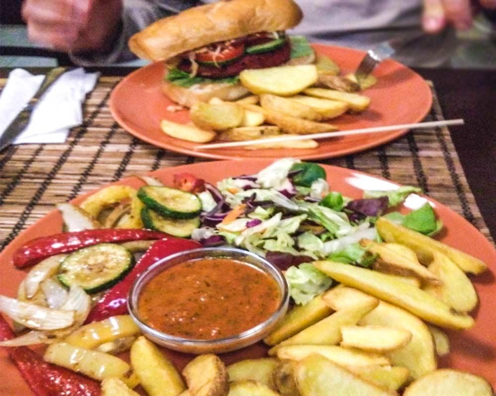 piatto misto con patatine fritte, insalata, verdure saltate e salsa budapest vegana e senza glutine