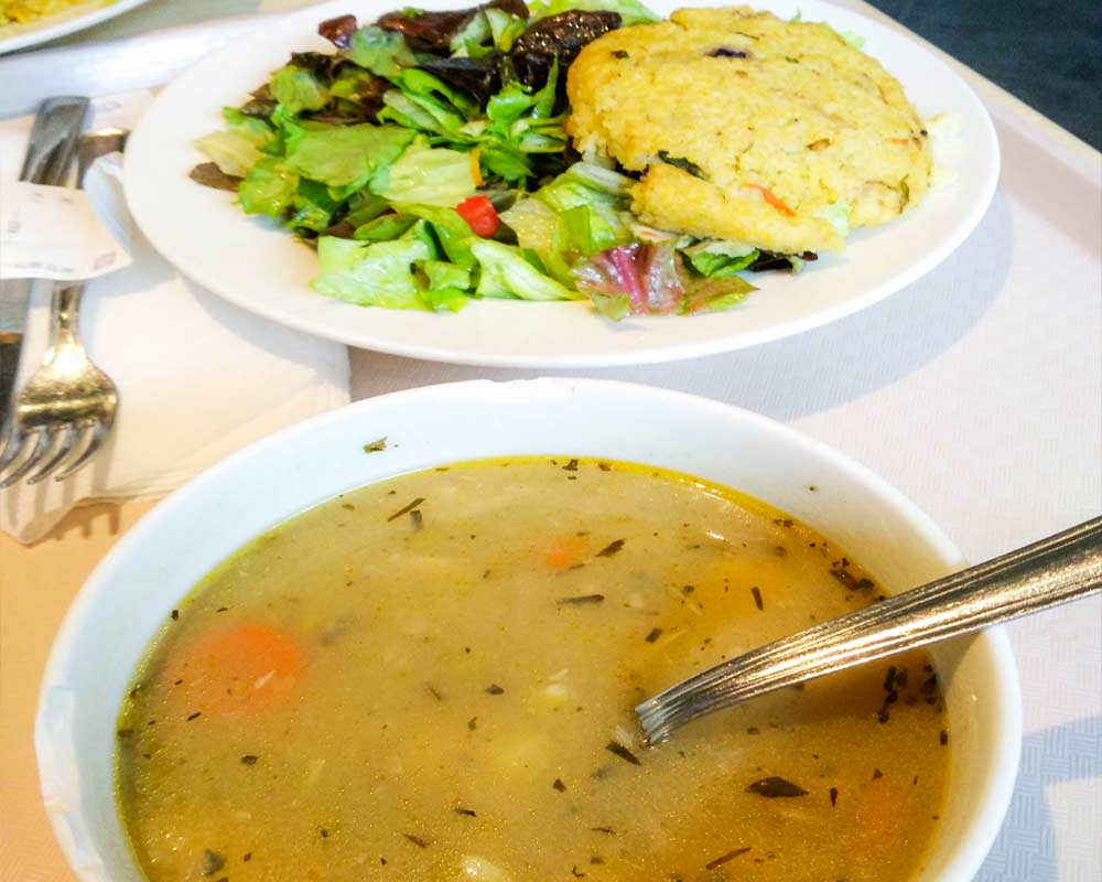 piatto con zuppa e uno con insalata e burger vegano senza glutine budapest vegana e senza glutine