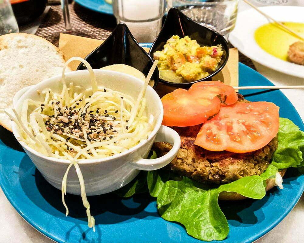 ciotola con insalata e burgher vegano accanto al ristorante quinoa
