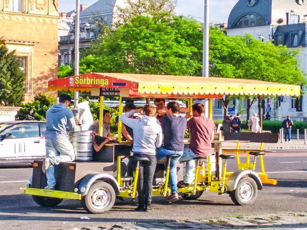 ragazzi che pedalano una bici bevendo birra a budapest