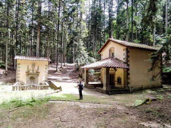 persona che fotografa la cappella e fonte di san gualberto nel bosco