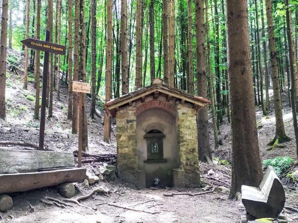 cappella di san sebastiano con panchine davanti in mezzo al bosco