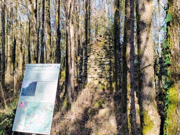 rovine di casa con cartello esplicattivo davanti sul sentiero della memoria monte scalari