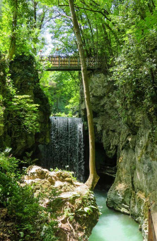 cascata nel bosco con ponte di legno sopra sul sentiero li vurgacci