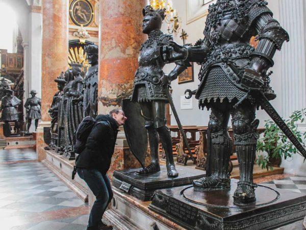 ragazzo davanti a delle statue nere dentro una chiesa