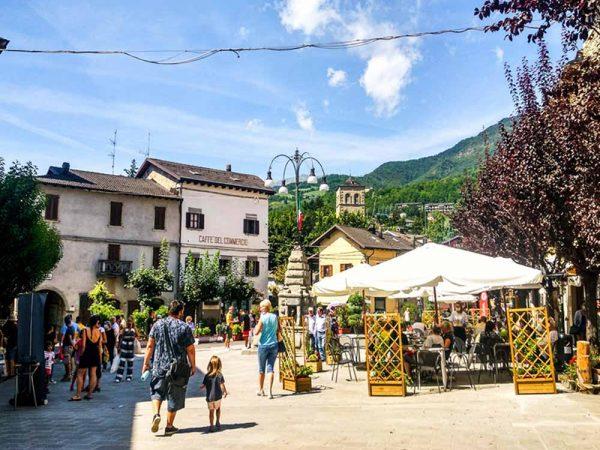 fanano piazza corsini con fontana in centro, palazzi e persone