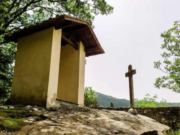 masso del diavolo in cima alla roccia con croce davanti e alberi alle spalle