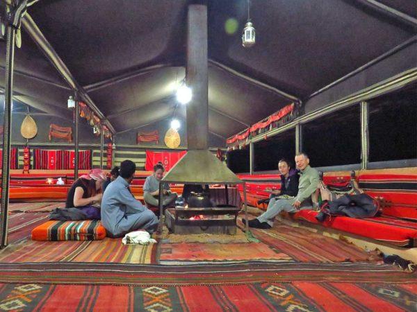sette persone intorno al fuoco all'interno della tenda beduida a milky way camp a wadi rum