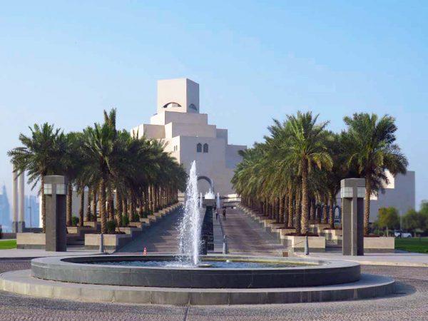 costruzione moderna del museo d'arte islamica con viale d'accesso fiancheggiato da palme