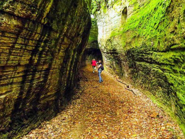 due persone all'interno di via cava nella necropoli di sovana