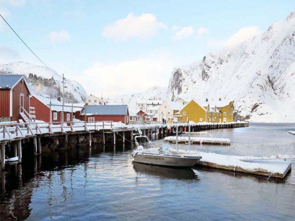 case colorate lungo il mare con le montagne innevate sullo sfondo a nusfjord