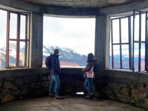 due persone che guardano le montagne dalla finestra dal rifugio