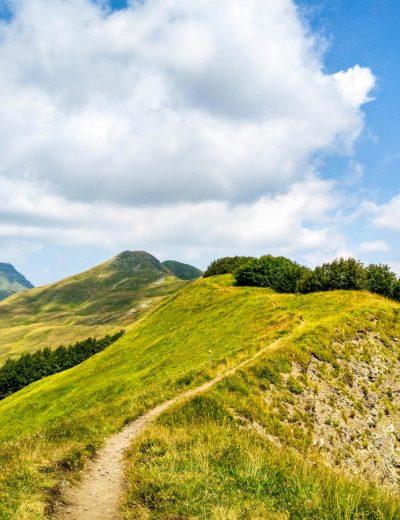 trekking sulla cima di montagna con il cielo azzurro e nuvole bianche nello sfondo