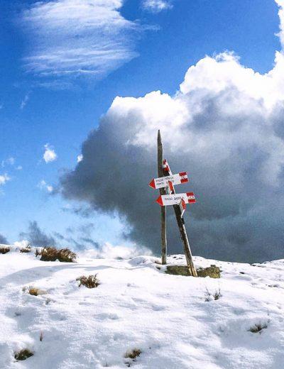 trekking sulla montagna innevata e indicazioni sentieri