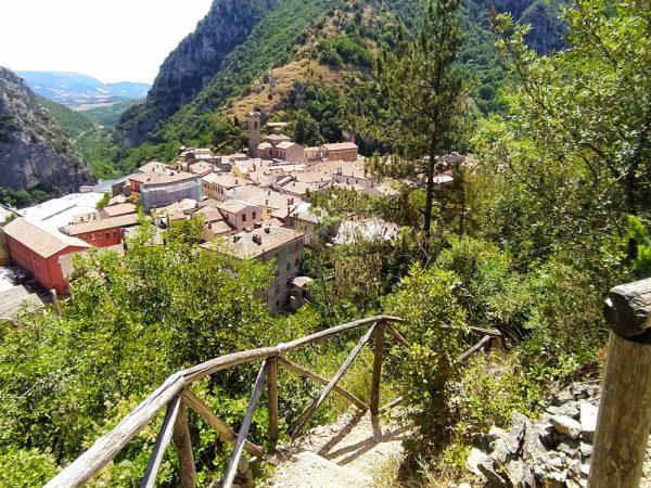 scalini che scendono nel bosco sul sentiero li vurgacci con la vista di pioraco sullo sfondo
