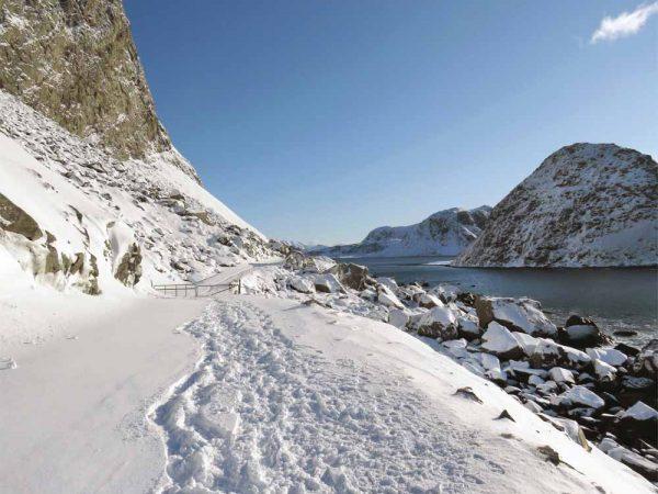 sentiero che costeggia la montagna lungo il mare con la neve
